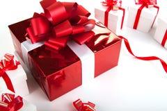 Подарочные коробки одной красной подарочной коробки белые на сером цвете Стоковое Изображение RF