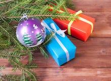Подарочные коробки связанные с лентами и шариком рождества под ветвью дерева Стоковые Фото