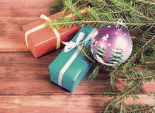 Подарочные коробки связанные с лентами и шариком рождества под ветвью дерева Стоковые Изображения RF