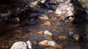 Подача речной воды между утесами и камнями в нажиме слайдера гор сток-видео