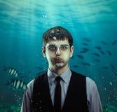 Подводная сцена бизнесмена с рыбами стоковая фотография