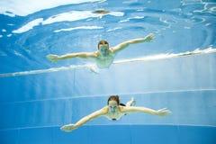 Подводный взгляд молодого заплывания пар в бассейне Стоковое фото RF