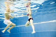 Подводный взгляд молодого заплывания пар в бассейне Стоковые Фото