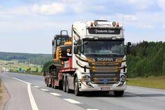 Подгонянное Scania R560 Semi тянет экскаватор вдоль скоростного шоссе Стоковые Фото