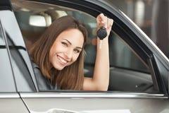 Подготавливайте для того чтобы получить на дороге. Привлекательная молодая женщина сидя на Стоковые Изображения RF