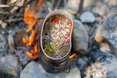 Подготавливать чай на лагерном костере. Стоковые Фотографии RF