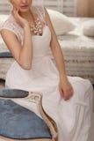 Подготовка венчания Красивая молодая невеста в белом свадьбы платья крупном плане внутри помещения Роскошное модельное усаживание Стоковая Фотография RF