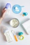 Подготовка младенца смеси подавая на белом взгляд сверху предпосылки Стоковое Изображение RF