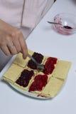 Подготовка домодельных тортов Женщина распространяет варенье на готовых тортах, лежа на плите Стоковые Фото