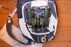 Подготовка для отключения, перемещения, рюкзака, биноклей, камеры, карты на деревянной предпосылке Стоковая Фотография RF