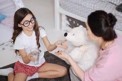 Полезная маленькая девочка и мать позаботить о игрушка дома Стоковая Фотография