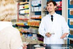 Полезная молодая женщина сервировки аптекаря в фармации Стоковые Изображения RF