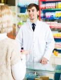 Полезная молодая женщина сервировки аптекаря в фармации Стоковое Изображение