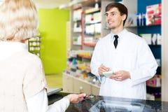 Полезная молодая женщина сервировки аптекаря в фармации Стоковые Фотографии RF