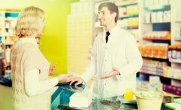 Полезная молодая женщина сервировки аптекаря в фармации Стоковое фото RF