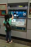 Маленькая девочка покупая билет MRT стоковое изображение rf