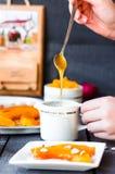 Полейте мед чайной ложки в керамических изделиях, испеченной тыкве, руках Стоковые Изображения RF