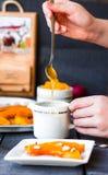 Полейте мед чайной ложки в керамических изделиях, испеченной тыкве Стоковая Фотография RF