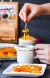 Полейте мед чайной ложки в керамических изделиях, испеченной тыкве Стоковая Фотография