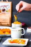 Полейте мед чайной ложки в керамических изделиях, испеченной тыкве Стоковые Фото