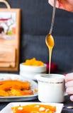 Полейте мед чайной ложки в керамических изделиях, испеченной тыкве Стоковое фото RF