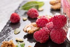 Поленики, мята, грецкие орехи и стекло коктеиля на черном столе Красивые розовые ягоды Целительные, вкусные, сладостные ягоды лет Стоковое Изображение