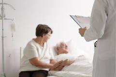 Поддерживая диагноз ` s доктора жены слушая Стоковые Изображения RF