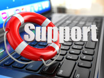 Поддержка. Компьтер-книжка и lifebuoy на клавиатуре компьтер-книжки. Стоковое фото RF