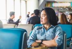 Полет азиатской женщины ждать на крупный аэропорт для отклонения Стоковое Изображение RF