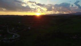Полет над зелеными холмами и деревней против красивого восхода солнца акции видеоматериалы