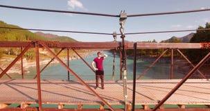 полет Средний-воздуха над туристом молодого человека оставаясь на висячем мосте и наблюдать сток-видео