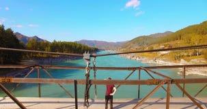 полет Средний-воздуха над туристом молодого человека оставаясь на висячем мосте и наблюдать видеоматериал