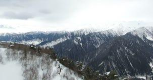 Полет трутня над подъемом лыжи с целью снег-покрытых гор покрытых с лесом в 4K сток-видео