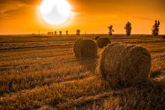 Поле захода солнца с связками сена Стоковая Фотография