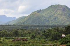 Поле и лес против больших горы и неба cloudys Стоковые Фотографии RF