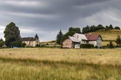 Поле на переднем крае с немного домов на краю поля Стоковые Изображения