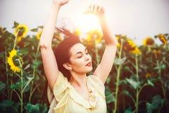 поле солнцецвета девушки брюнет расслабляющее внешнее близко Стоковое Изображение RF