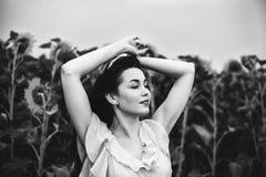 поле солнцецвета девушки брюнет расслабляющее внешнее близко Стоковые Фото