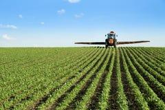 Поле урожая сои трактора распыляя стоковые изображения