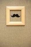 Поддельный усик в деревянной рамке на предпосылке одежды из твида Стоковые Фото