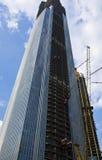 Под зданиями конструкции с кранами башни на голубом небе Стоковое Фото