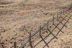 Подлинные деревянные обнести бросания сельской местности тень на песочной почве во время восхода солнца Стоковые Фото