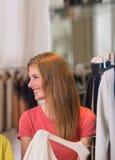 Подлинные красивые покупки женщины в магазине одежды Стоковая Фотография