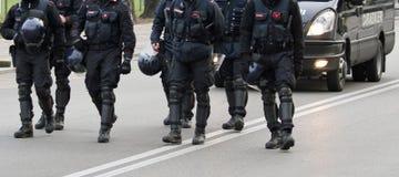Полисмены пока марширующ совместно в середине дороги Стоковое Фото