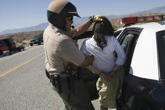 Полисмен арестовывая женского запойного водителя Стоковая Фотография
