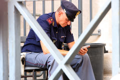 Полисмен на его усаживании сотового телефона Стоковые Изображения RF