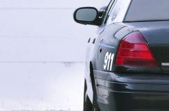 Полицейская машина припаркованная перед белым гаражом Стоковое Изображение