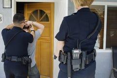 Полицейский арестовывая молодого человека Стоковая Фотография RF