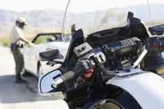Полицейский говоря к водителю остановленного автомобиля Стоковые Изображения