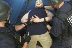 Полицейский кладя наручники на руки преступника Стоковая Фотография